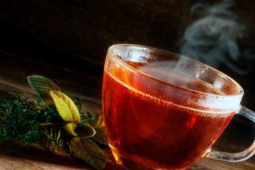 стеклянная кружка с горячим чаем на столе и трава