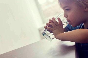 маленький мальчик пьет из большого стеклянного стакана воду